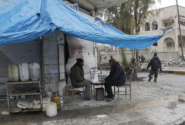 Street vendors warm themselves around a fire as they sell fuel during cold weather in the rebel-controlled area of Maaret al-Numan town in Idlib province, Syria January 4, 2016. (Photo by Khalil Ashawi/Reuters)