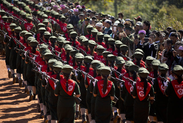 In this January 12, 2015 photo, a female troops of Ta'ang National Liberation army (TNLA) march during a function in Mar Wong, northern Shan state, Myanmar, marking the anniversary of their insurrection from the government just over a half-century ago. (Photo by Gemunu Amarasinghe/AP Photo)