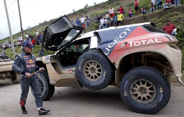 Carlos Sainz of Spain walks next to his Peugeot as he arrives at the bivouac at the end of the fourth stage in the Dakar Rally 2016 in Jujuy province, Argentina, January 6, 2016. (Photo by Marcos Brindicci/Reuters)