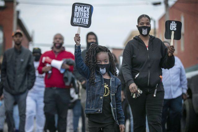 Six-year-old Diamond Wood marches through the streets of downtown Elizabeth City, N.C., Friday, April 23, 2021. Several days of protests followed the shooting death of Andrew Brown Jr. on Wednesday by sheriff's deputies serving drug-related search and arrest warrants. (Photo by Robert Willett/The News & Observer via AP Photo)