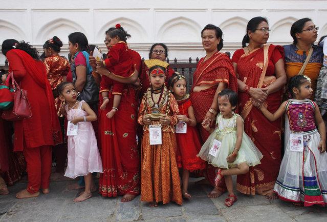 Young Nepalese girls with their mothers wearing new cloths wait for Kumari puja at Hanuman Dhoka, Basantapur Durbar Square, Katmandu, Nepal, Tuesday, September 17, 2013. (Photo by Niranjan Shrestha/AP Photo)