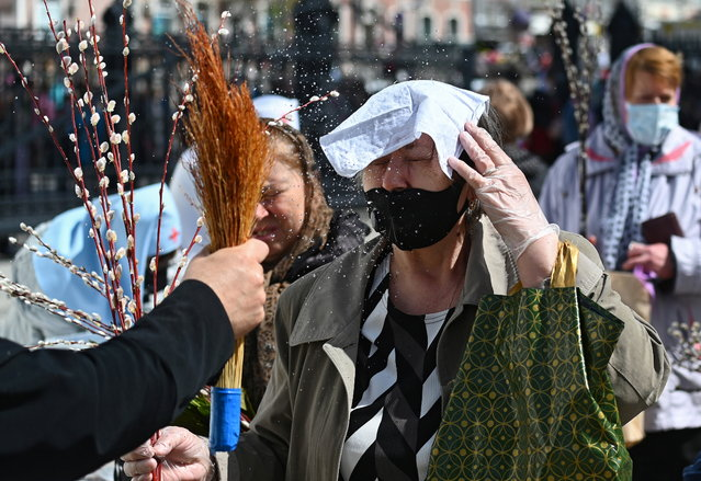 Believers are sprayed with holy water during a service, which marks the Orthodox feast of Palm Sunday, amid the coronavirus disease (COVID-19) outbreak in Rostov-on-Don, Russia on April 25, 2021. (Photo by Sergey Pivovarov/Reuters)