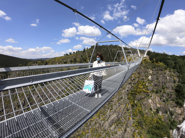 A woman walks across a narrow footbridge suspended across a river canyon, which claims to be the world's longest pedestrian bridge, in Arouca, northern Portugal, Sunday, May 2, 2021. (Photo by Sergio Azenha/AP Photo)