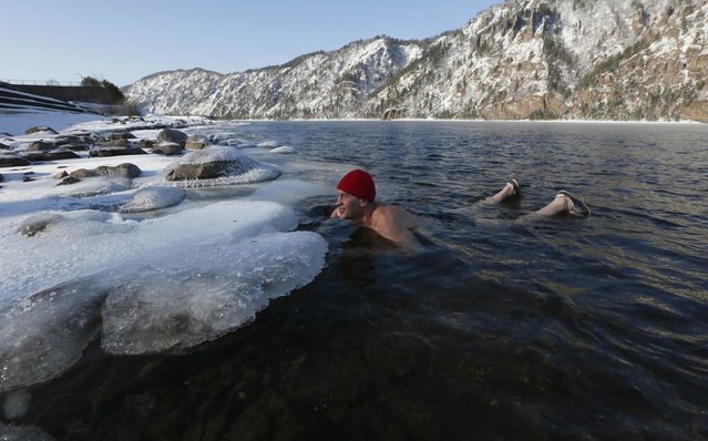 Vladimir Korabelnikov, head of a local orphanage and a member of local winter swimming club, swims in the waters of the Yenisei River, with the air temperature at about minus 20 degrees Celsius (minus 4 degrees Fahrenheit), in the town of Divnogorsk near Krasnoyarsk, Siberia, February 20, 2015. (Photo by Ilya Naymushin/Reuters)
