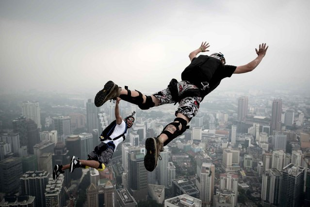 Base jumper David Laffargue (R) and Rodolphe Roger Coianiz (L) from France leap from the 300-meters Open Deck of the Malaysia's landmark Kuala Lumpur Tower during the International Tower Jump in Kuala Lumpur on September 27, 2013. (Photo by Mohd Rasfan/AFP Photo)