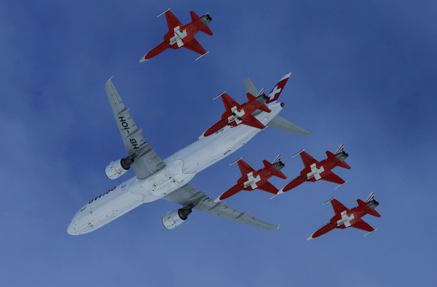 Members of the Swiss aerobatic team Patrouille Swiss fly in formation with a Swiss Airbus A 320 over the men's Alpine Skiing World Cup Super Combined race in Wengen, Switzerland January 15, 2016. (Photo by Denis Balibouse/Reuters)