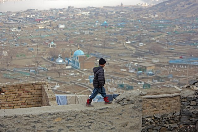 Obaidullah, a 10-year-old Afghan boy, walks on the wall of his home on the outskirts of Kabul, Afghanistan, Thursday, February 5, 2015. (Photo by Rahmat Gul/AP Photo)