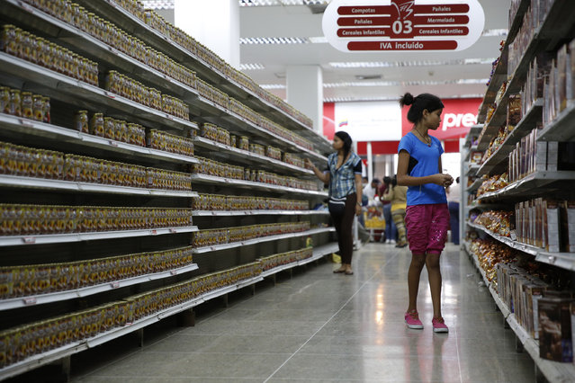 People walk past shelves mostly filled with the same product at a state-run supermarket in Caracas January 9, 2015. (Photo by Carlos Garcia Rawlins/Reuters)