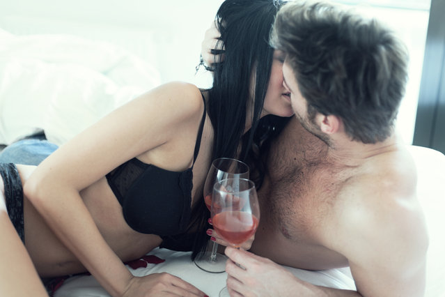 Young couple drinking wine in the bed. (Photo by Juhasz Peter/Getty Images)