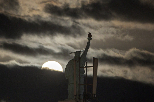 The moon rises over a replica of Statue of Liberty in Kosovo capital Pristina on Tuesday, April 27, 2021. This moon is a supermoon, meaning it appears larger than an average full moon because it is nearer the closest point of its orbit to Earth. (Photo by Visar Kryeziu/AP Photo)