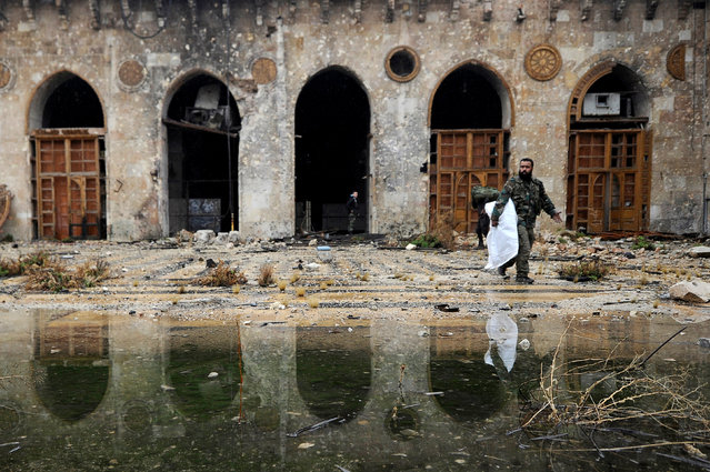 A member of forces loyal to Syria's President Bashar al-Assad walks inside the Umayyad mosque, in the government-controlled area of Aleppo, during a media tour, Syria December 13, 2016. (Photo by Omar Sanadiki/Reuters)