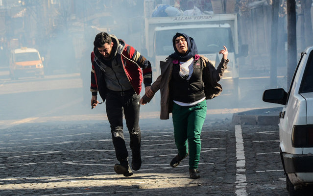 """Residents run for cover from tear gas fired by security forces after new curfews were imposed in the Sur district of Diyarbakir on January 27, 2016. Turkish security forces are subjecting residents of Kurdish-dominated southeastern Turkey to """"collective punishment"""" with military operations backed by curfews, Amnesty International said last week, accusing the army of """"recklessly"""" using excessive force. (Photo by Ilyas Akengin/AFP Photo)"""