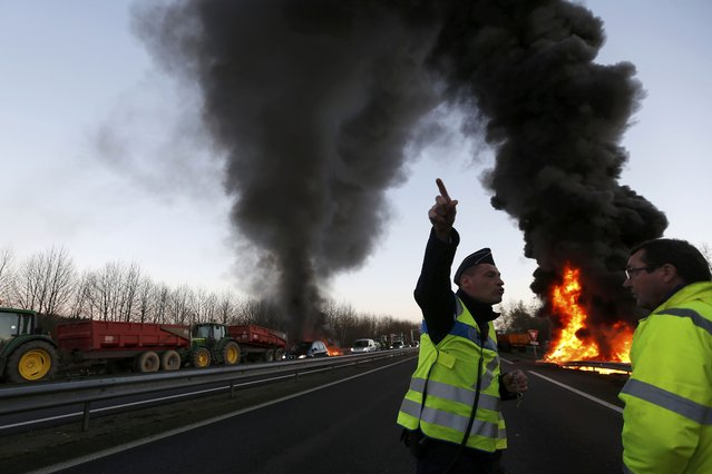 A French gendarme reacts as French livestock farmers burn tyres to protest falling prices near on a road in Tinteniac, western France, January 28, 2016. (Photo by Stephane Mahe/Reuters)