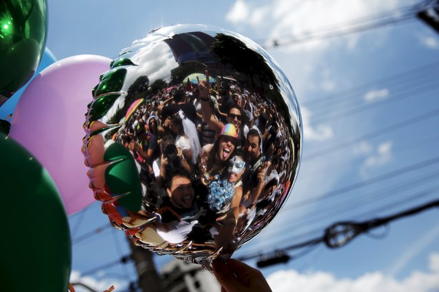 """Revellers are reflected in a balloon as they pose for a photo while taking part in the annual carnival block party known as """"Casas comigo"""" or """"Marry me"""" at the Pinheiros neighborhood in Sao Paulo, Brazil, January 30, 2016. (Photo by Nacho Doce/Reuters)"""