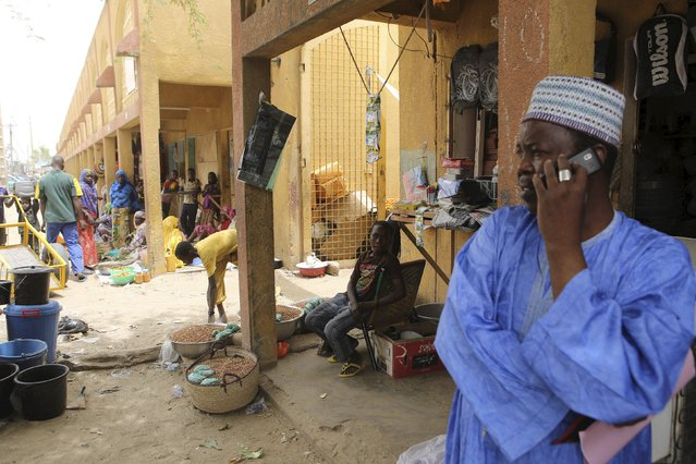 A city official (R) makes a phone call at the main market in Diffa, March 23, 2015. (Photo by Joe Penney/Reuters)