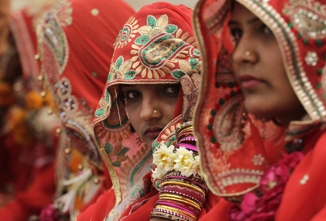 A bride adjusts her veil during a mass marriage ceremony in Ahmadabad, India, Saturday, March 21, 2015. 112 Muslim couples from impoverished families tied the knot in a single ceremony organized by a social organization. (Photo by Ajit Solanki/AP Photo)
