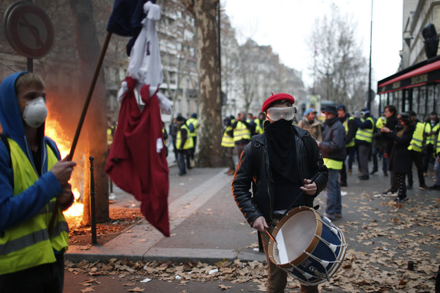 A demonstrator plays a drum Saturday, December 8, 2018 in Paris. (Photo by Rafael Yaghobzadeh/AP Photo)