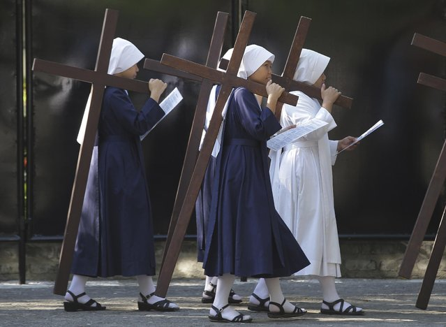 Filipino nuns carry wooden crosses as they make the Stations of the Cross at the Philippine Center of Saint Pio of Pietrelcina on Wednesday, April 1, 2015 in suburban Quezon city, east of Manila, Philippines. Devotees practice different religious rites during the Holy Week in this predominantly Roman Catholic country. (Photo by Aaron Favila/AP Photo)