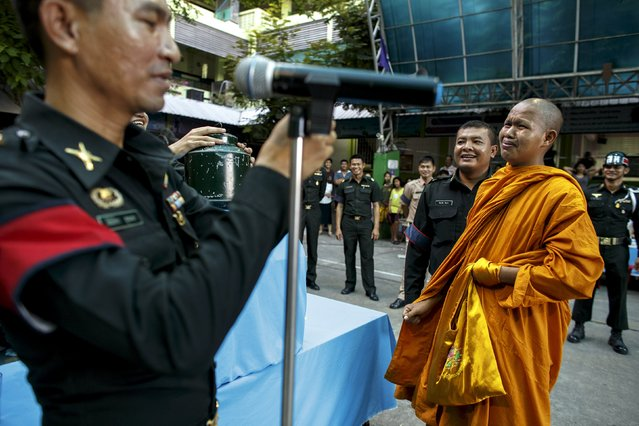 A Buddhist monk reacts after picking a ticket during an army draft held at a school in Klong Toey, the dockside slum area in Bangkok April 5, 2015. (Photo by Athit Perawongmetha/Reuters)