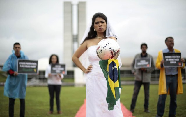 "Members of NGO Rio de Paz, uses an woman dressed as a bride during a protest in front of the National Congress, comparing the delay of works for the World Cup with the delay of the bride for the wedding, in Brasilia December 6, 2013. The NGO Rio de Paz, criticized the Brazilian government with the posters saying: ""FIFA standard stadium, standard planning Brazil"" and ""Demanding excellence in public administration"". (Photo by Ueslei Marcelino/Reuters)"