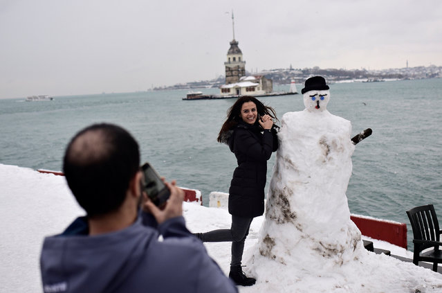 A woman poses with a snowman, with the Maiden's Tower in the background, in Istanbul, Turkey January 10, 2017. (Photo by Yagiz Karahan/Reuters)