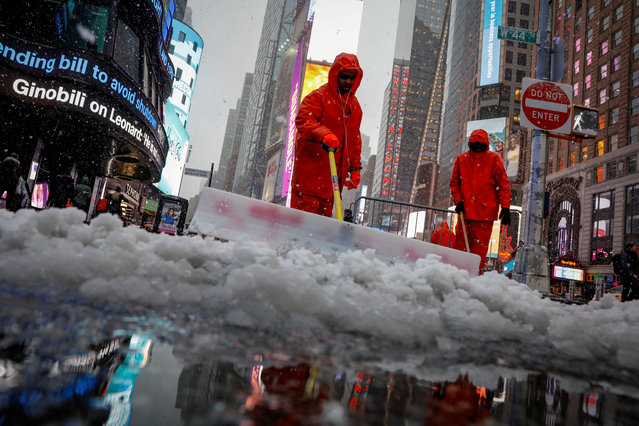 Workers clear snow during a winter nor'easter storm in Times Square in New York City, U.S., March 21, 2018. (Photo by Brendan McDermid/Reuters)