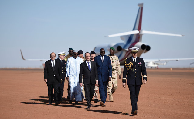 French President Francois Hollande (4th L) walks with Malian Prime Minister Modibo Keita (C) and Chief of the Defence Staff, French army General Pierre de Villiers (3rd R) as he arrives on January 13, 2017 to visit the troops of France' s Barkhane counter- terrorism operation in Africa' s Sahel region in Gao, northern Mali. .François Hollande said on January 13, 2017 that the fight against jihadists was the same in Sahel, Iraq and Syria as in France, during a meeting with French troops in northern Mali. (Photo by Stephane de Sakutin/AFP Photo)