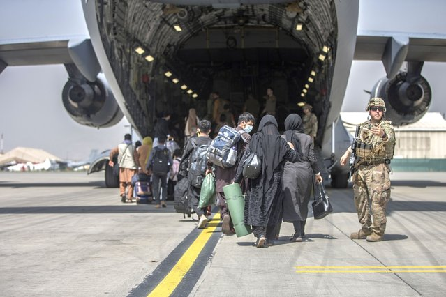 In this image provided by the U.S. Marine Corps, families begin to board a U.S. Air Force Boeing C-17 Globemaster III during an evacuation at Hamid Karzai International Airport in Kabul, Afghanistan, Monday, August 23, 2021. (Photo by Sgt. Samuel Ruiz/U.S. Marine Corps via AP Photo)