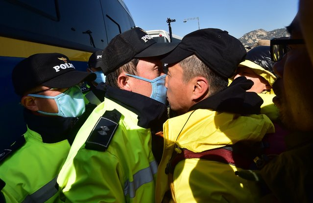A relative (R) of the victims of South Korea's Sewol ferry disaster is in a nose-to-nose stand-off with a policeman (L) during an anti-government protest near the presidential residence in Seoul on April 17, 2015. Dozens of people continued their protests overnight after thousands of mourners rallied to mark the first anniversary of the disaster that claimed 304 lives. (Photo by Jung Yeon-Je/AFP Photo)