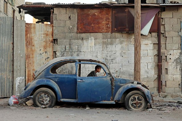 A Palestinian boy plays inside an old car in Gaza City on August 5, 2021. (Photo by Mohammed Abed/AFP Photo)