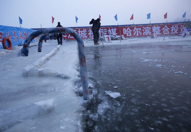 A worker breaks ice on a pool carved into the thick ice covering the Songhua River in the early morning as he prepares the Harbin Ice Swimming Competition in the northern city of Harbin, Heilongjiang province ce January 5, 2014. (Photo by Kim Kyung-Hoon/Reuters)