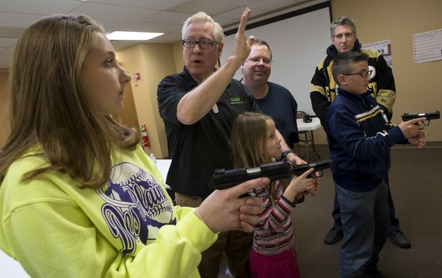 Instructor Jerry Kau (C) shows students Samantha Dolatowski (L), Joanna Zuber and Sam Minnifield (front on R) how to hold a handgun during a Youth Handgun Safety Class at GAT Guns in East Dundee, Illinois, April 21, 2015. (Photo by Jim Young/Reuters)