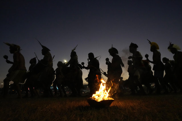 """Indigenous men perform a ritual dance as Indigenous groups set up the """"Luta pela Vida"""" or Struggle for Life camp, in Brasilia, Brazil, Monday, August 23, 2021. The groups arrive to the capital for a weeklong Struggle for Life mobilization to protests against a Supreme Court ruling that could undermine rights to their lands, and against President Jair Bolsonaro's government. (Photo by Eraldo Peres/AP Photo)"""