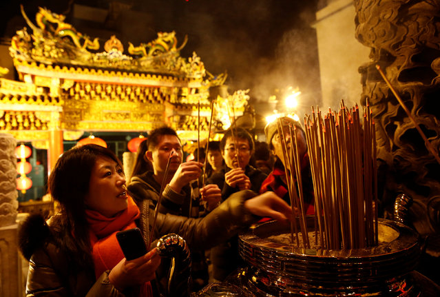 People burn incense sticks at a temple as they celebrate the Lunar New Year in China Town, in Yokohama, south of Tokyo, Japan January 28, 2017. (Photo by Kim Kyung-Hoon/Reuters)