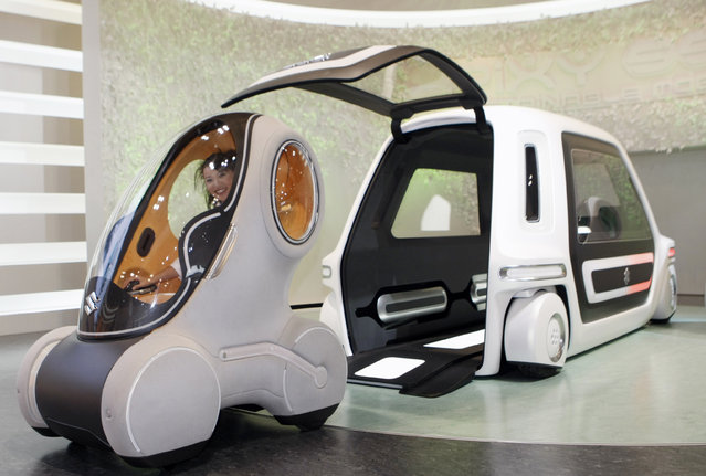 """Suzuki's one-person electric vehicle """"Pixy"""" comes out of the """"SSC"""" (Suzuki Sharing Coach) at a ddemonstration of the concept commuter models during the 40th Tokyo Motor Show in Chiba Thursday, October 25, 2007. (Photo by Kim Kyung-Hoon/Reuters)"""