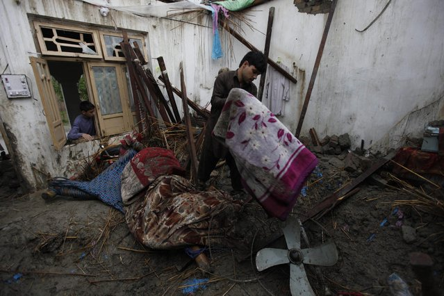 People try to salvage their belongings from their home following torrential rains in Peshawar, Pakistan, 27 April 2015. (Photo by Bilawal Arbab/EPA)