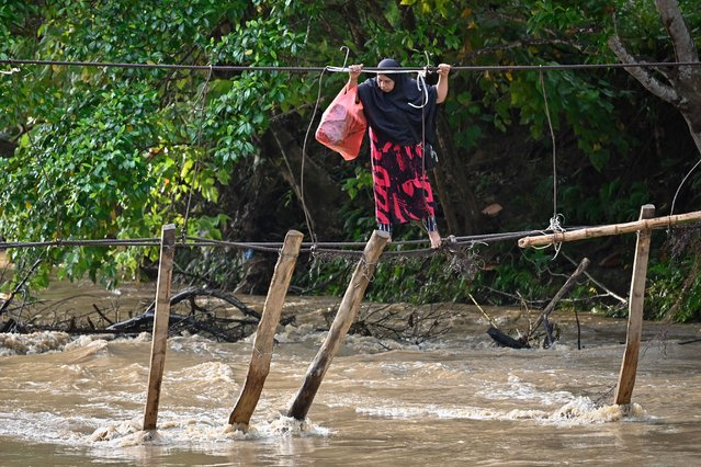 A woman crosses a river using the remains of a bridge, swept away during flooding the previous year, at Malela village in Luwu Regency, South Sulawesi on September 13, 2021. (Photo by Hariandi Hafid/AFP Photo)