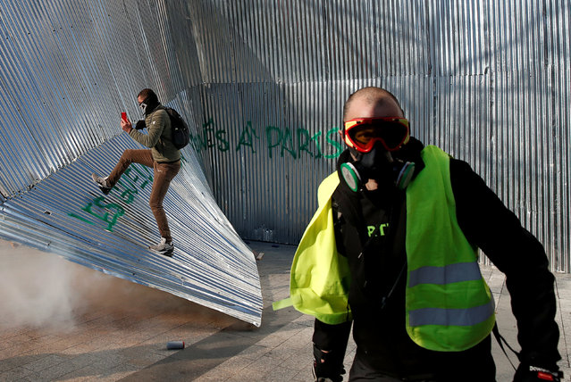 """A protester wearing a yellow vest walks in front of demolished metal fencing during a demonstration by the """"yellow vests"""" movement in Paris, France, March 16, 2019. (Photo by Benoit Tessier/Reuters)"""