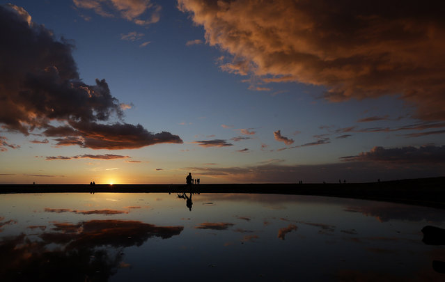 A man walks his dogs past a puddle as the sun sets at Ocean Beach in San Francisco, Saturday, February 28, 2015. (Photo by Jeff Chiu/AP Photo)