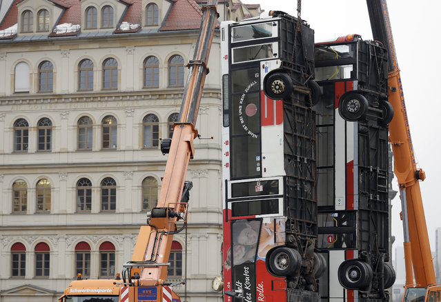 """A worker stands in front of the first two of total three buses close to the """"Frauenkirche"""" church, left, in the center of the east German city of Dresden, Germany, Monday, February 6, 2017.  A Syrian artist is placing the three buses upright on a square in the eastern German city of Dresden, to evoke the suffering of civilians in the Syrian city of Aleppo. Manaf Halbouni's work """"Monument"""" is being erected in front of Dresden's Frauenkirche church. It mirrors a barrier made of three buses placed on a street in Aleppo to protect residents from sniper fire. (Photo by Michael Sohn/AP Photo)"""