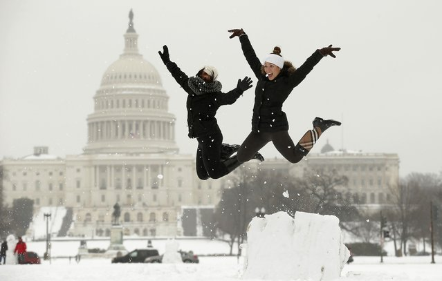 Adrienne Sipe (L) and Brooke Gilliam of Washington D.C. leap off a snow podium they made near the U.S. Capitol in Washington February 13, 2014. A deadly and intensifying winter storm packing heavy snow, sleet and rain pelted a huge swath of the U.S. East Coast on Thursday, grounding flights and shuttering schools and government offices. (Photo by Kevin Lamarque/Reuters)