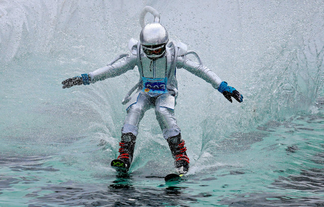 A skier in a festive costume attempts to cross a pool of water at the foot of a ski slope while competing in the annual Gornoluzhnik amateur event to mark the end of the ski season at the Bobrovy Log ski resort in the suburbs of the Siberian city of Krasnoyarsk, Russia, April 14, 2019. (Photo by Ilya Naymushin/Reuters)