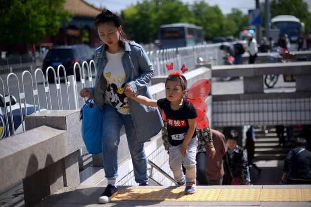 A family walks out of an underpass near the Forbidden City in Beijing on May 3, 2015. (Photo by Wang Zhao/AFP Photo)