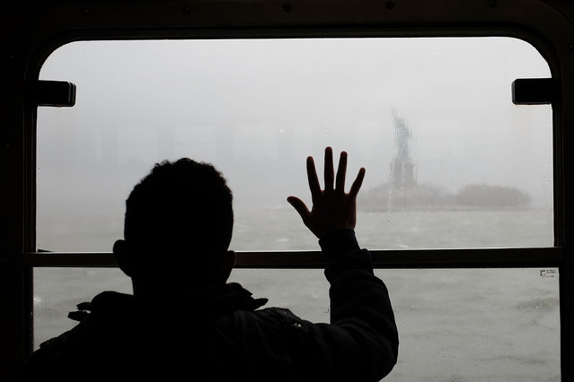 A man looks out at the Statue of Liberty in the rain and fog from the Staten Island Ferry on April 20, 2015 in New York City. (Photo by Spencer Platt/Getty Images)