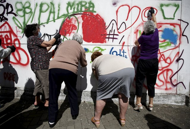 Women spray their designs on a wall during a graffiti class offered by the LATA 65 organization in Lisbon, Portugal May 14, 2015. (Photo by Rafael Marchante/Reuters)