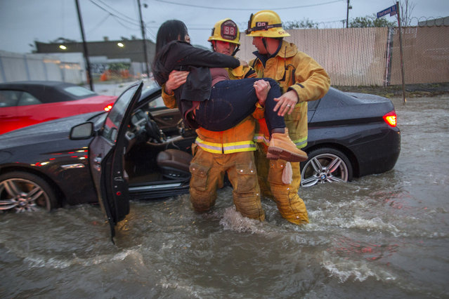 A firefighter carries a woman from her car after it was caught in street flooding as a powerful storm moves across Southern California on February 17, 2017 in Sun Valley, California. (Photo by David McNew/Getty Images)