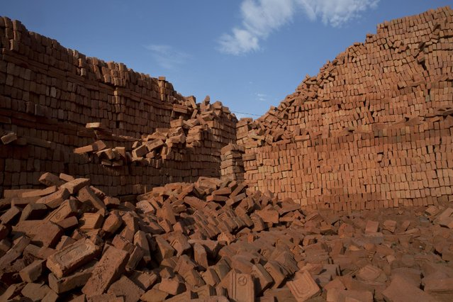 In this Thursday, May 14, 2015 photo, bricks are piled up in stacks at a brick factory in Bhaktapur, Nepal. (Photo by Bernat Amangue/AP Photo)