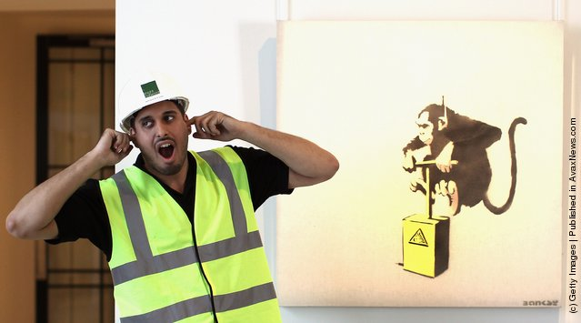 A workman jokes besides a work entitled 'Monkey Detonator'  by  Banksy