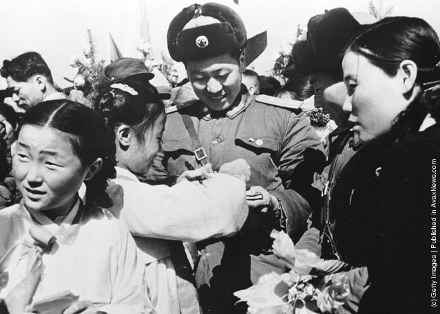 1958: Korean girls present a member of the Chinese People's Volunteer Army with a bouquet of flowers prior to the mass withdrawal of Chinese troops from North Korea