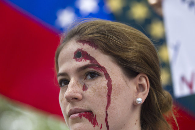 An anti-government demonstrator, with a bleeding bullet hole drawn on her forehead, takes part in a protest in front of an office of the Organization of American States, OAS, in Caracas, Venezuela, Friday, March 21, 2014. Opposition lawmaker Maria Corina Machado is scheduled to speak before the OAS council in a closed-door session Friday in Washington D.C., presenting the situation in her country where at least 28 people have been killed in daily anti-government protests that began in early February. (Photo by Esteban Felix/AP Photo)